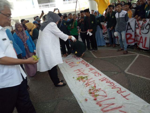 Bunda Indah Tabur Bunga dengan Tangan Diperban di Kain Kafan Bertuliskan Pemerintah